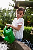 Little girl filling watering can from well