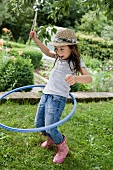 Girl playing with a hula hoop in a garden