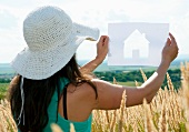 Woman holding up cut-out paper silhouette of house against landscape