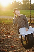 Girl sitting on a tyre swing in park