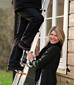 Woman holding ladder for husband