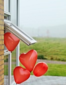 Heart-shaped balloons floating out of window