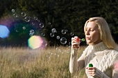 Woman blowing soap bubbles in wheat field