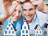 Couple holding bunch of keys above model houses