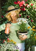 Senior woman holding pot of flowers