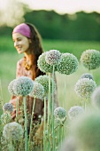Young woman, focus on allium flowers in foreground