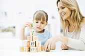 Little girl stacking blocks, mother watching and smiling