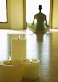 Yoga class, candles burning while person sits in lotus position in blurred background
