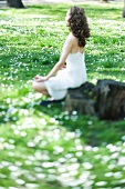 Young woman sitting in lotus position in meadow, side view, selective focus
