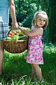 Little girl standing beside older sibling, holding large basket full of produce, cropped view