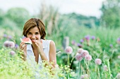 Young woman in garden, eating piece of watermelon