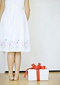 Girl standing next to gift