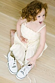 Little girl kneeling on ground near pair of shoes, looking surprised