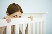 Woman peeking over side of crib at camera
