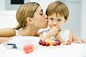 Mutter mit kleinem Sohn am beim Essen eines Obstdesserts