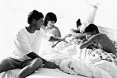Family having pillow fight in bed, black and white