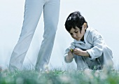Little boy squatting down on grass looking at flower next to woman's legs
