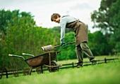 Mann mit Schubkarre bei der Gartenarbeit