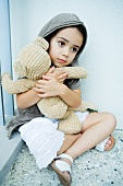 Little girl sitting on floor, clutching teddy bear