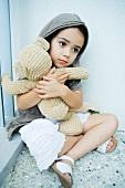 Kind mit Teddybär im Arm sitzt vor der Hauswand