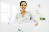 Teen girl carrying recycling bin full of plastic bottles, smiling at camera