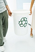 Two people carrying recycling bin together, cropped view