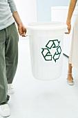 Junges Paar trägt Recyclingtonne
