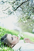 Teenage girl lying on the ground, smelling flower, looking up