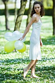 Young woman walking in field of flowers, holding balloons behind back, looking over shoulder