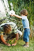 Little boy pouring water on his father's head as he works in garden