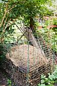 Kompostbehälter aus Maschendrahtgitter mit Gartenabfällen