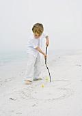 Kleiner Junge am Strand zeichnet mit einem Holzstecken