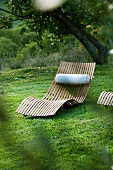 Sun lounger made of curved wooden slats with neck cushion in garden