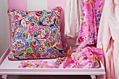 Colourful, ethnic-style cushion on console table next to dresses hanging up