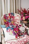 Colourful scarf on Rococo-style armchair next to flower arrangement
