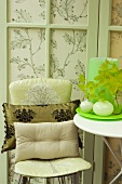 Cushions on chair against patterned fabric screen