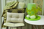 Cushions on chair and side table holding vases on tray
