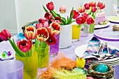 Multicoloured, decorated dining table with bouquets of flowers and colourful Easter decorations