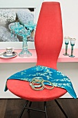 Modern chair decorated with bangles and silk scarf in front of glassware on shelf