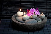 Meditative atmosphere in spa - orchid flowers and lit pebble candles in stone dish