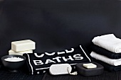 Simple, black and white spa decoration with soaps and lettering on towel