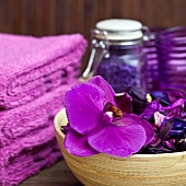 Violet still-life in spa room - orchid flowers in bamboo dish next to stacked towels
