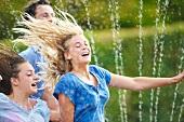 Friends running through sprinkler spray in garden