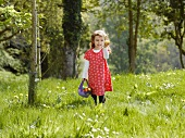 A girl looking for Easter eggs in a meadow