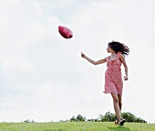 Teenager holding heart-shaped balloon in meadow