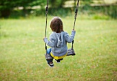 Child playing on swing in garden