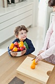 A mother cutting oranges and a boy holding a bowl of fruit