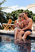 Couple sitting on edge of swimming pool holding drinks