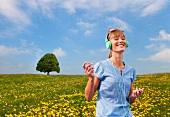 Woman listening to music through earphones in a meadow of dandelions