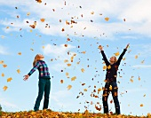 Mother and daughters throwing fallen autumn leaves into the air